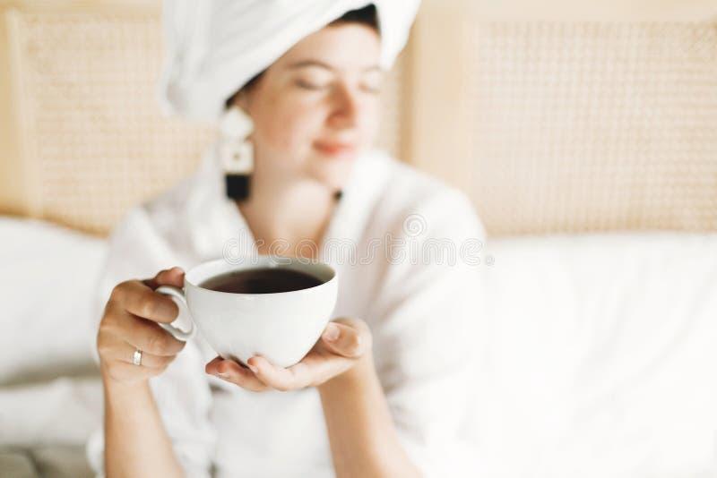 Copo branco com café ou chá no close up das mãos das meninas Chá bebendo da jovem mulher feliz bonita na cama na sala de hotel ou fotografia de stock royalty free