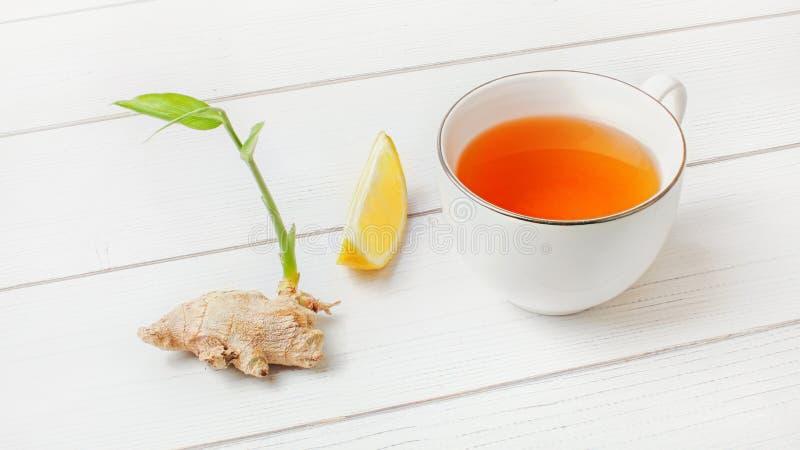 Copo branco com chá ambarino quente, limão e raiz seca do gengibre com mola verde ao lado dela, nas placas brancas imagem de stock royalty free