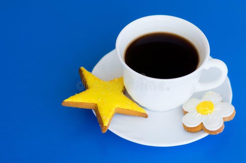 Copo branco com os biscoitos do café e do gengibre em um fundo azul imagens de stock