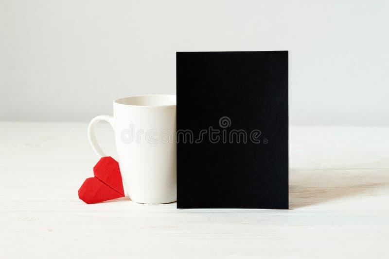 Copo branco, coração do origâmi e cartão vazio de papel preto com espaço da cópia Caneca no fundo de madeira Dia do `s do Valenti fotos de stock royalty free