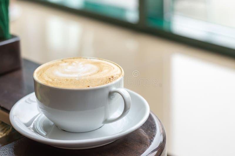Copo branco do cappuccino com arte do latte Café na tabela de madeira ao lado da janela do café imagens de stock royalty free