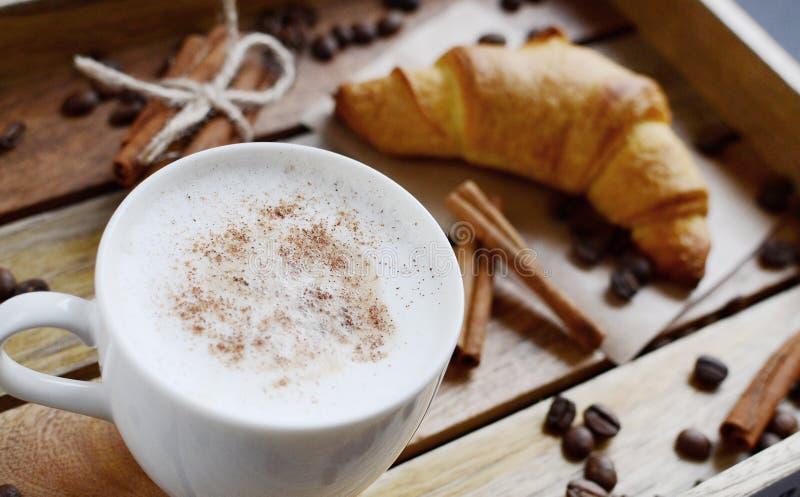 Copo branco do cappuccino e do croissant na bandeja de madeira imagens de stock royalty free