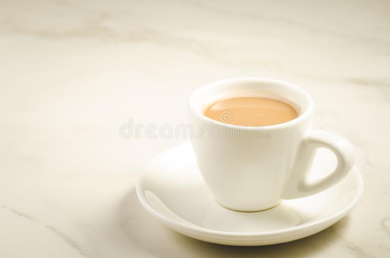 Copo branco do chá com leite/copo branco do chá com leite em um fundo de mármore, em um foco seletivo e em um espaço da cópia imagens de stock