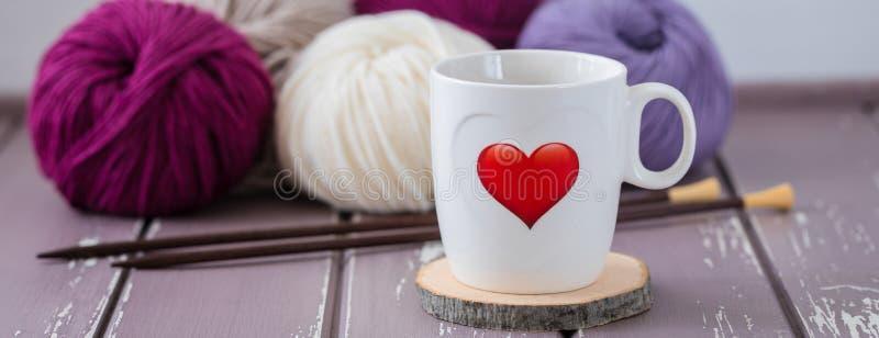Copo branco do chá com um coração vermelho no fundo de lãs de confecção de malhas coloridas e de agulhas de madeira fotos de stock royalty free