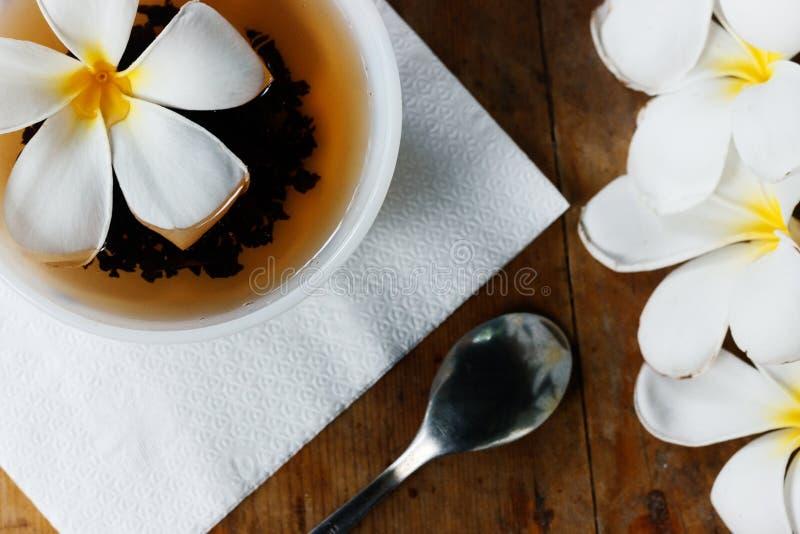 Copo branco do chá de Ceilão e do Plumeria exótico amarelo das flores - fundo liso do ` s de Sri Lanka da configuração com a tabe fotografia de stock royalty free