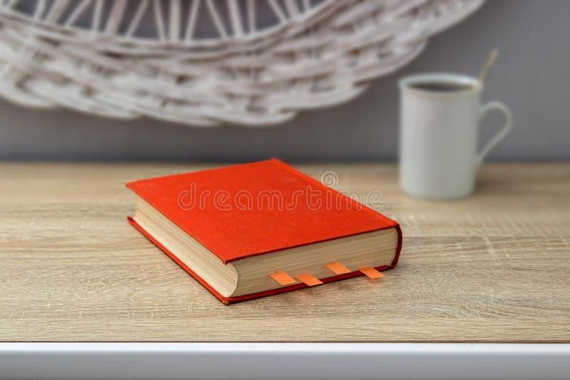 Copo branco do chá e um livro aberto em uma tabela de madeira Um potenciômetro vermelho com a árvore verde no fundo foto de stock