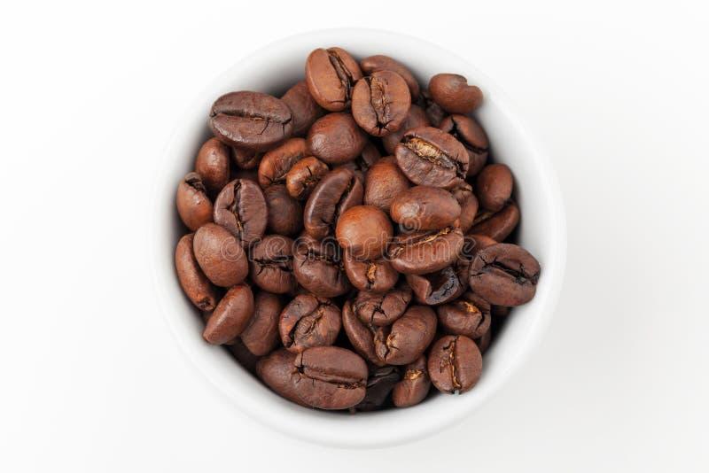 Copo branco pequeno do café completamente de feijões de café roasted frescos fotografia de stock
