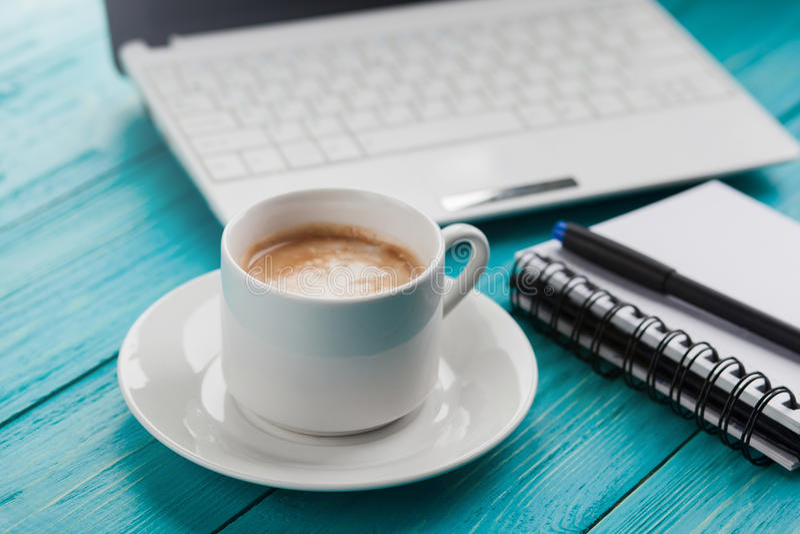 Copo, caderno e portátil de café no backgrou de madeira de turquesa imagens de stock