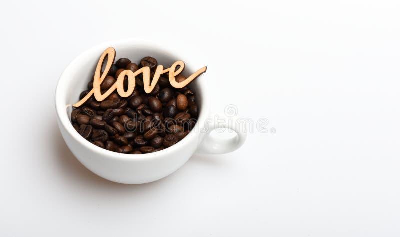Copo cerâmico com feijões de café e amor de madeira da palavra Ruptura de café romântica Feijões de café da caneca no fundo branc fotos de stock