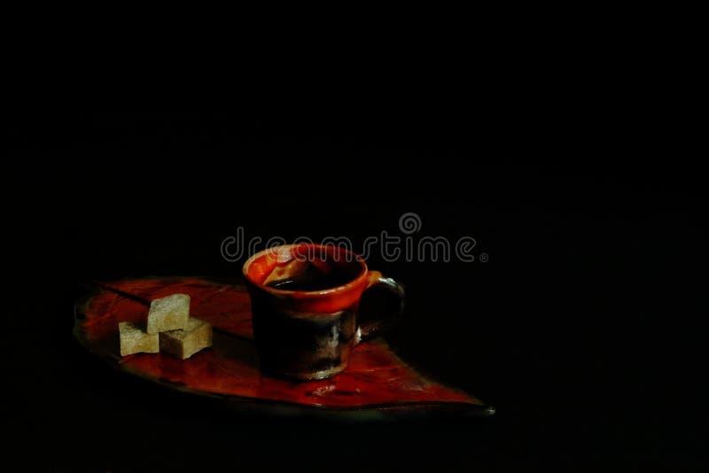 Copo cerâmico decorado com crosta de gelo com café e partes aromáticos fortes de açúcar de bastão na bandeja na forma da folha no fotos de stock