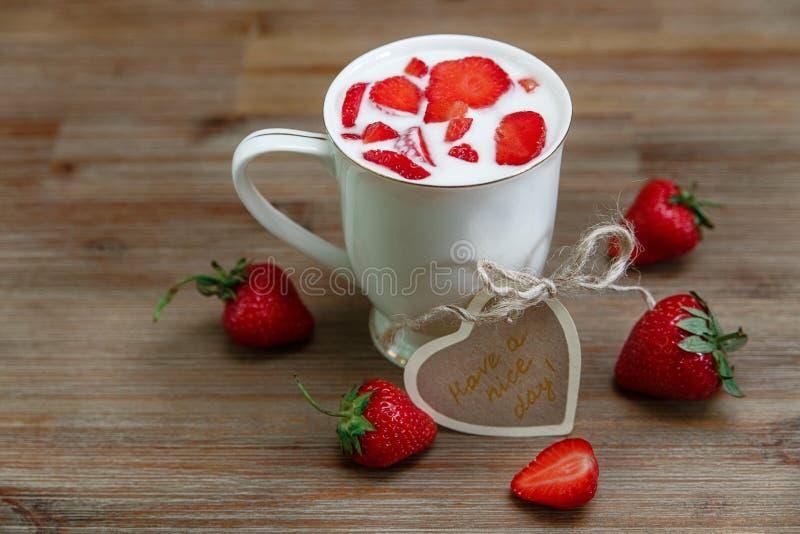 Copo cerâmico do leite, morangos frescas vermelhas, cartão do desejo no fundo de madeira Alimento saboroso saudável orgânico do c fotos de stock royalty free