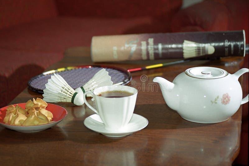 Copo, chá, biscoitos, petecas do badminton, raquete imagens de stock