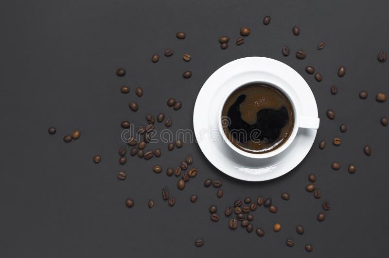 Copo colocado liso do café preto e dos feijões de café no espaço escuro cinzento da cópia da opinião superior do fundo Conceito d imagem de stock