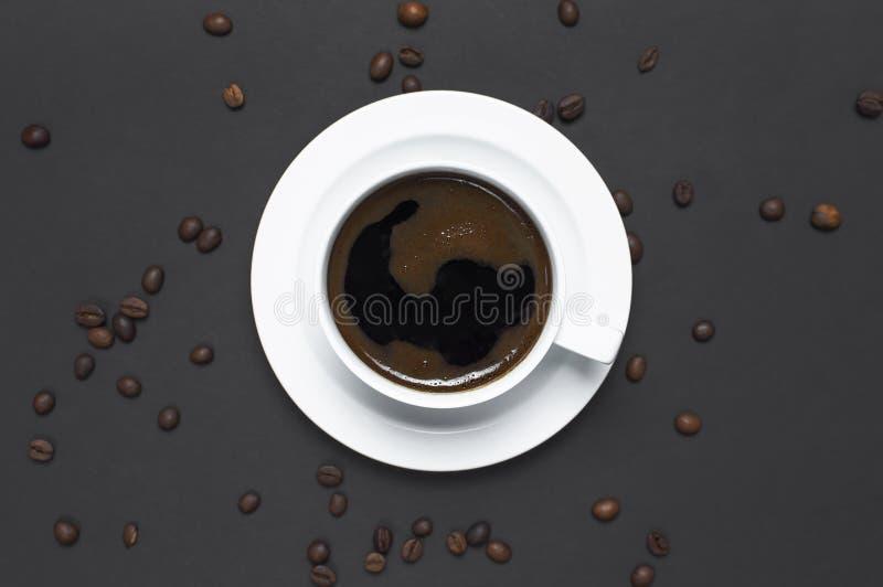 Copo colocado liso do café preto e dos feijões de café no espaço escuro cinzento da cópia da opinião superior do fundo Conceito d fotografia de stock royalty free