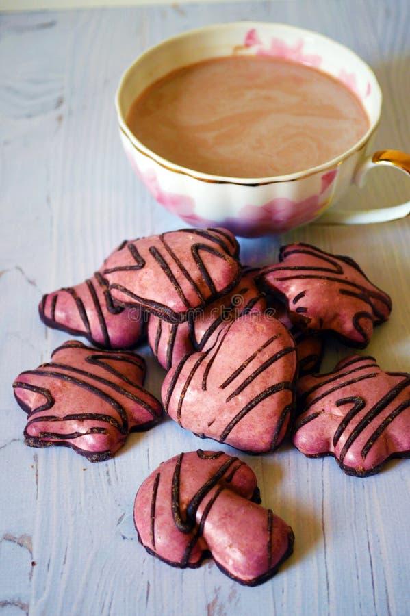 Copo com as cookies aromáticas do cacau e do gengibre com esmalte do açúcar em um fundo de madeira foto de stock