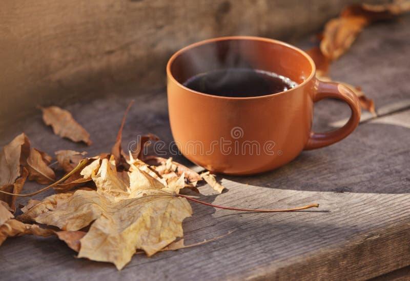 Copo com bebida quente em um outono de madeira do fundo imagem de stock