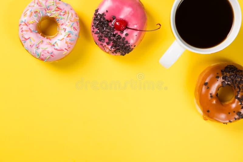 Copo com café e anéis de espuma no fundo amarelo Vista superior e espaço livre para seu texto imagem de stock royalty free