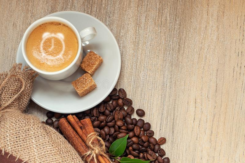 Copo com café com feijões de café, saco de serapilheira, sinal do despertador da canela no fundo de madeira claro fotos de stock royalty free