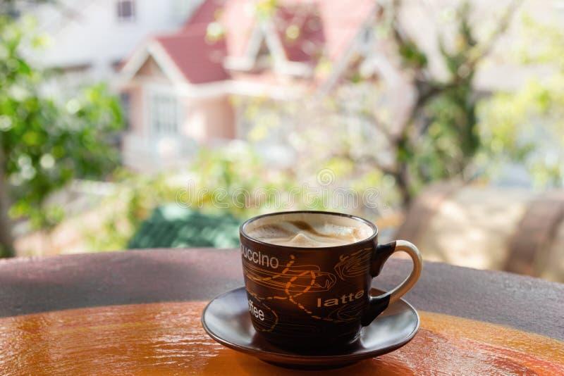 Copo com café quente do leite em uma tabela colorida de madeira colorida em um café no fundo da opinião da cidade foto de stock