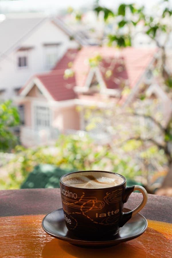 Copo com café quente do leite em uma tabela de madeira colorida em um café no fundo da opinião da cidade imagem de stock
