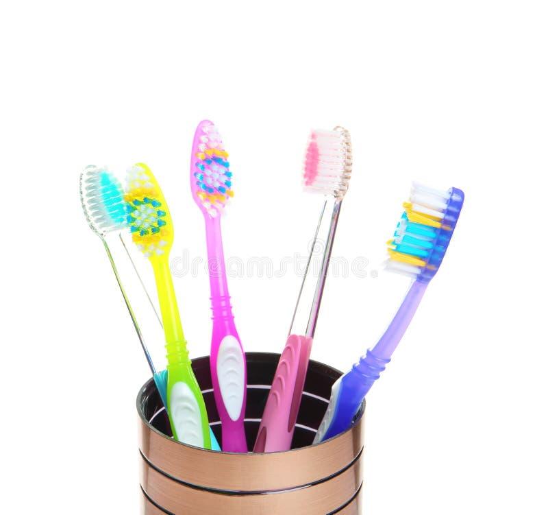 Copo com escovas de dentes diferentes imagem de stock