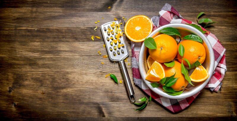 Copo com laranjas frescas, entusiasmo e ralador na tela fotografia de stock