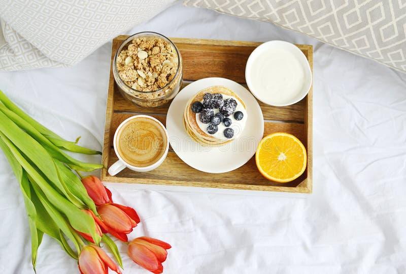 Copo com o café da manhã saudável alaranjado do cappuccino e do Granola caseiro das bagas do creme de leite das panquecas imagens de stock