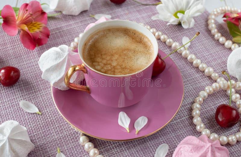 Copo cor-de-rosa com café e as pétalas frescos entre pérolas, flores e doces imagem de stock