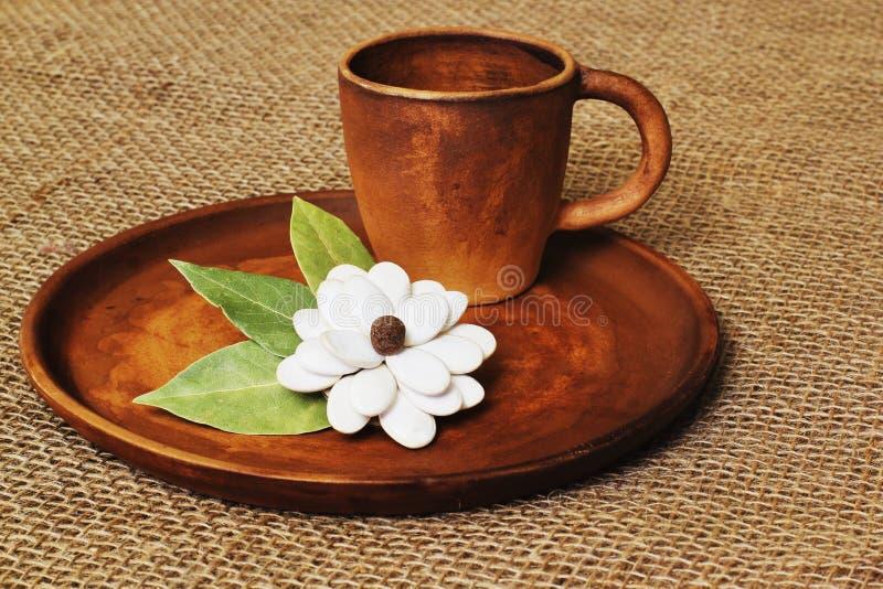 Copo da argila do café e flor caseiro original das sementes e das folhas de louro de abóbora na bandeja cerâmica redonda na lona  foto de stock royalty free