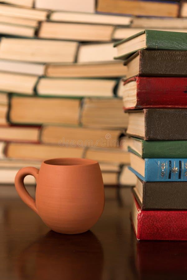 Copo da argila e muitos livros em uma tabela de madeira foto de stock royalty free