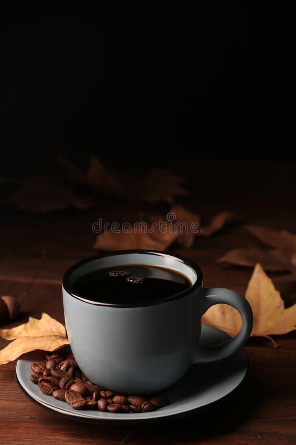 Copo da bebida acolhedor quente com feijões de café e folhas de outono fotografia de stock