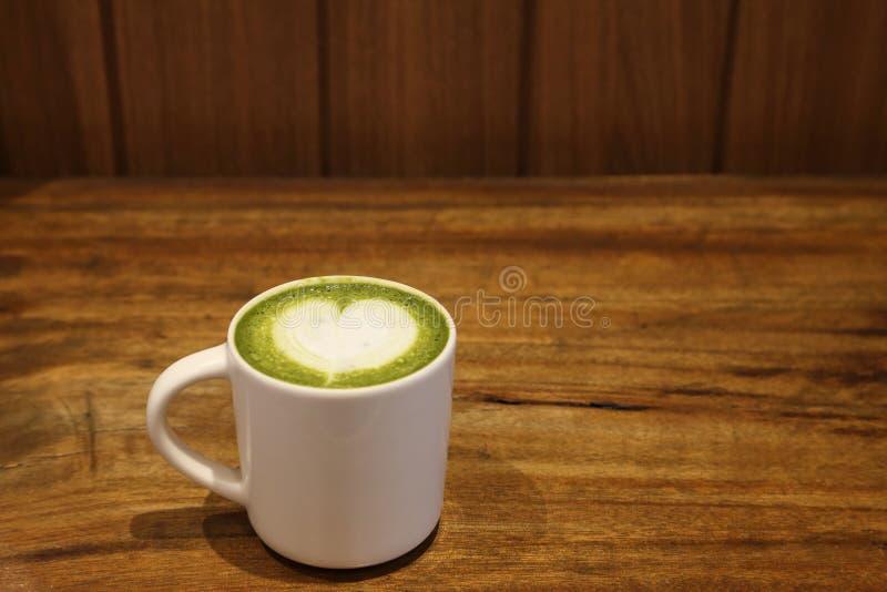 Copo da bebida quente da arte do latte do chá verde do matcha para o amante no Valentim com leite dado forma coração da espuma da imagens de stock royalty free
