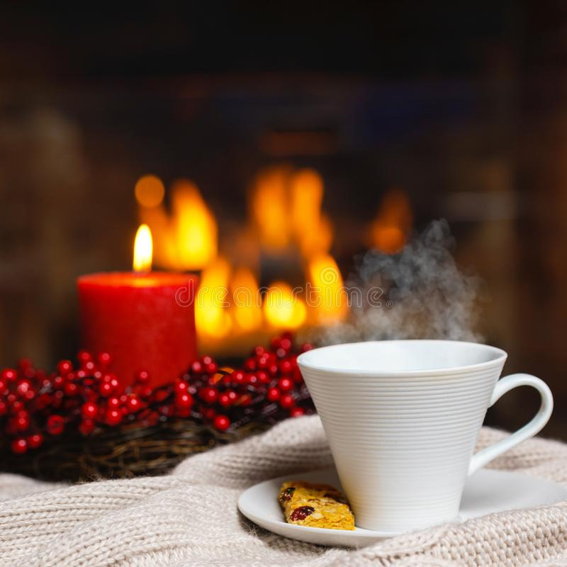 Copo da bebida quente com vela vermelha das bagas do vapor e da cookie em Chr imagem de stock royalty free
