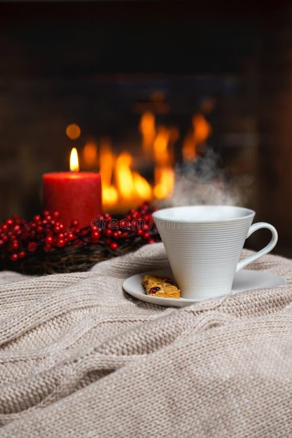 Copo da bebida quente com vela vermelha das bagas do vapor e da cookie em Chr fotos de stock royalty free