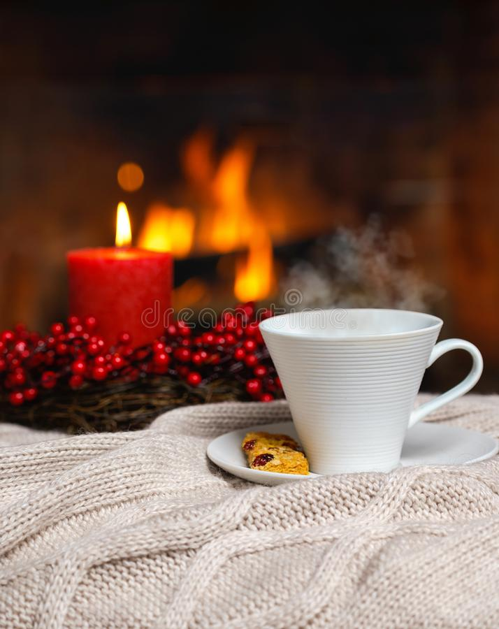 Copo da bebida quente com vela vermelha das bagas do vapor e da cookie em Chr imagem de stock