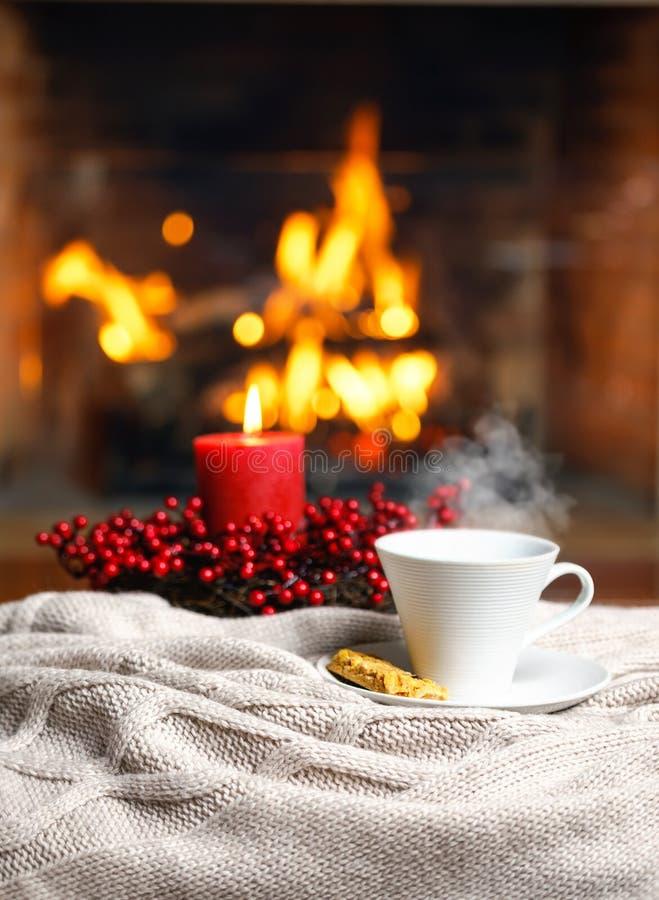 Copo da bebida quente com vela vermelha das bagas do vapor e da cookie em Chr fotografia de stock