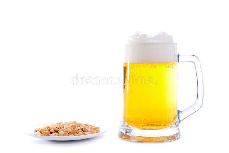 Copo da cerveja e do saucer com amendoins imagens de stock