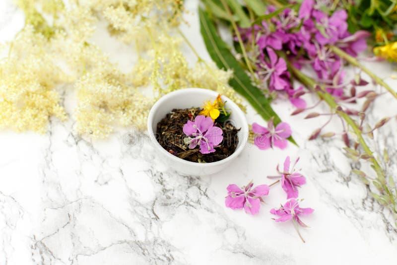 Copo da porcelana com Ivan-chá erval seco com azaléia e prados foto de stock