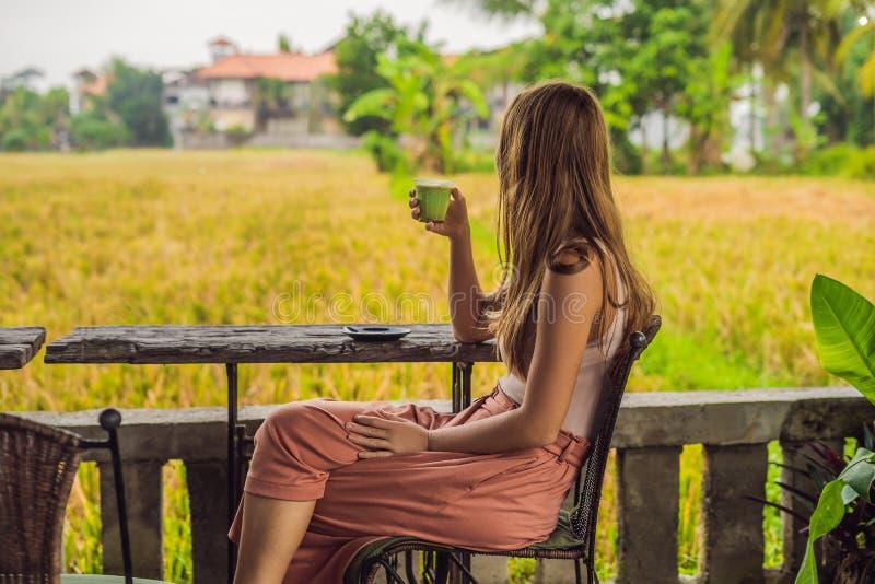 Copo da terra arrendada da jovem mulher do Latte do matcha, chá verde, na tabela de madeira velha do fundo imagem de stock