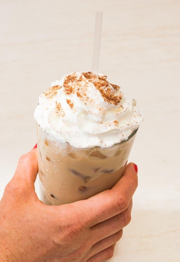 Copo da terra arrendada da mão do café congelado espumoso com palha imagem de stock royalty free