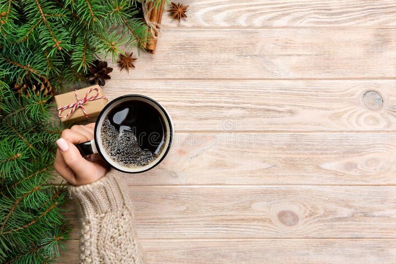 Copo da terra arrendada da mulher do café quente na tabela de madeira rústica mãos na camiseta morna com caneca, manhã do inverno fotos de stock