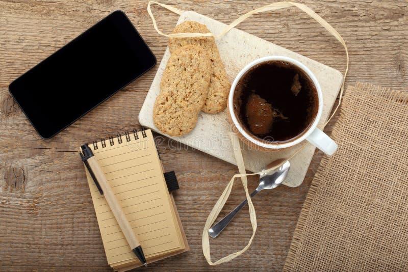 Copo da xícara de café com a cookie crocante na tabela e no pho esperto foto de stock