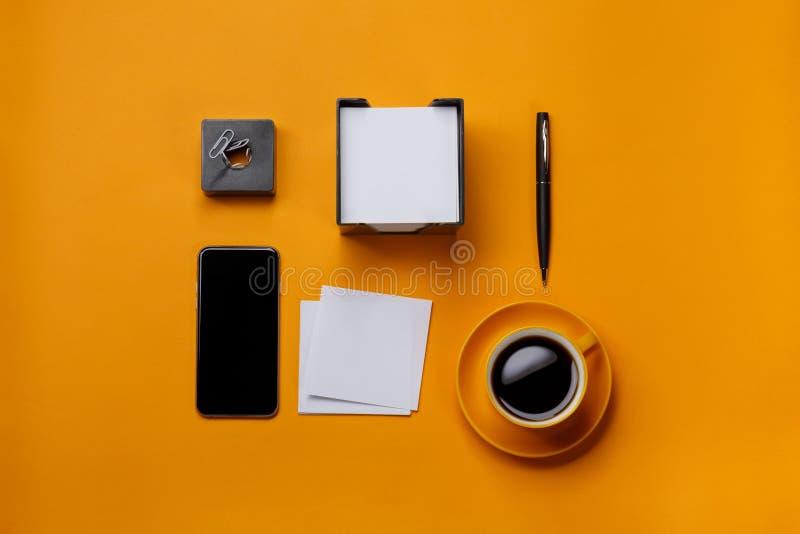 Copo de café amarelo p do papel de nota do telefone do negócio do desktop do fundo fotografia de stock royalty free