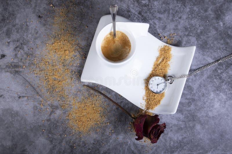 Copo de café branco da porcelana com açúcar mascavado, o relógio seco da rosa, do açucareiro, da rosa e de bolso foto de stock royalty free