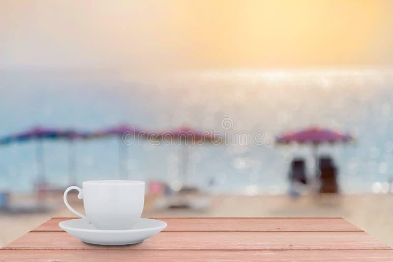 Copo de café branco na tabela de madeira com a praia b do mar do cenário do borrão imagem de stock royalty free