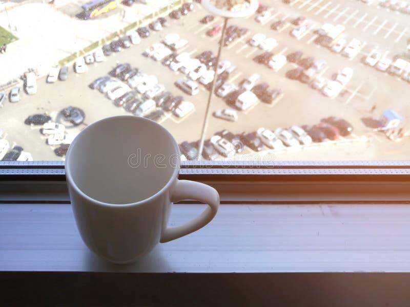 Copo de café branco no peitoril da janela de alumínio fotos de stock