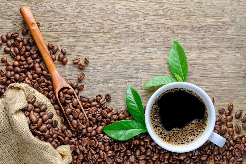 Copo de café com feijões, a colher de madeira, o saco do saco do cânhamo e a folha verde na tabela de madeira foto de stock royalty free