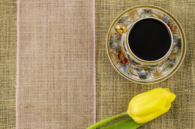 Copo de café com flor e fita cor-de-rosa no fundo de linho imagens de stock