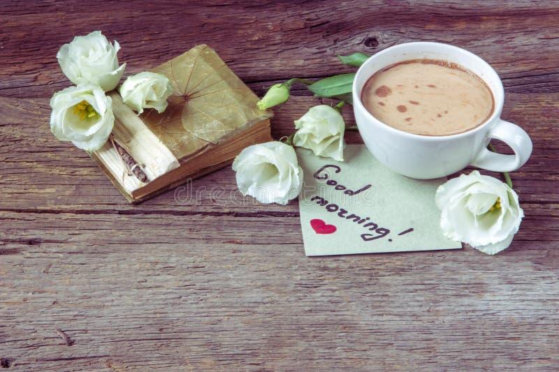 Copo de café com o lisianthus da flor da mola e o bom dia das notas fotografia de stock