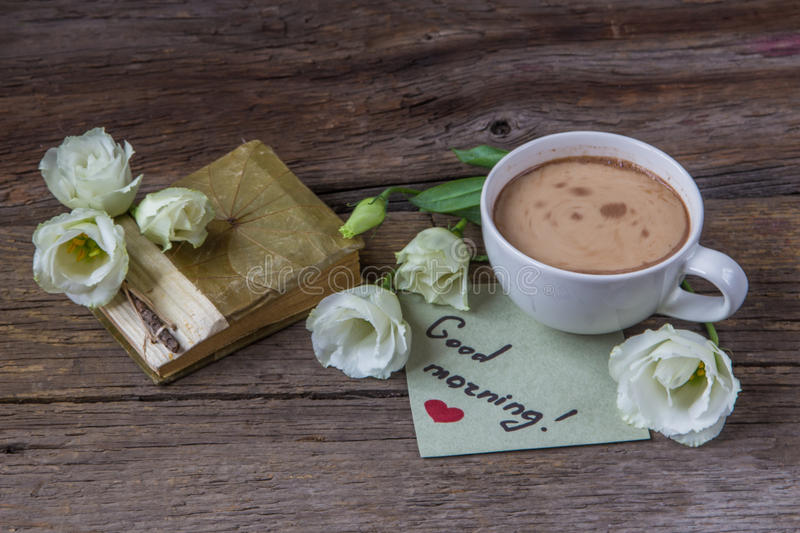 Copo de café com o lisianthus da flor da mola e o bom dia das notas fotos de stock
